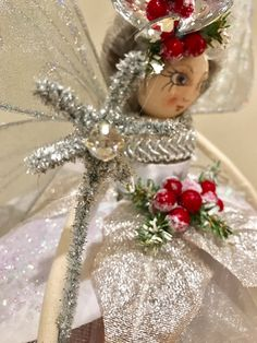Meet Hollyberry- one of my luxury Ooak Fairy Christmas Tree Top fairies. She is dressed in a gown of glittered petals which are arranged over layers of tulle and organza. Her bodice is edged with silver brocade. Her merino wool hair is windswept and upon her head and bound with twigs, berries and glittering crystals. In her hand she carries her jewelled wand. Her legs are painted in the signature striped stocking of the Fabulous Fairy Creations. Her handmade double wings are large and…