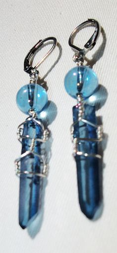 The focal of these ear rings are beauitful gemstone crystal points. These double terminated points are beautiful blue, Celestial Indigo Aura quartz. This is an amazingly beautiful type of quartz that has been fused with Indium. The Indium fuses with the quartz (not just a coating that will wear off). The end result is a indigo blue/purple color with an iridescent rainbow shine.  The crystal points have been wire wrapped in sterling silver and attached to Stainless Steel (hypo-allergenic)…