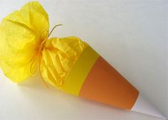 Roll paper to make a cone and then fill with colored tissue paper. Tie with a ribbon.
