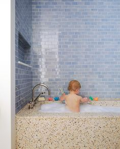 """In the kids' bathroom, Alexis Stewart used terrazzo for the tub and chose cornflower-blue tile for the walls with longevity in mind. """"It's a cute color for kids, but they can grow up with it,"""" she says. """"You don't want to have to retile later because your kids' bathroom is bubblegum pink with little flowers all over."""""""