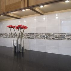 We are planning a similar design in our kitchen. White subway tile on either side of a glass decorative mosaic center. Ours will be stainless steel+blue glass+white crystal rock. Our new Ikea under-cabinet lights should really show them off well