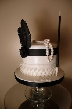 Black and white 'flapper' cake complete with ruffles, pearls, a feather headpiece and a cigarette stick! ♥