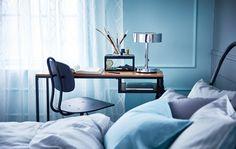 Metallinen ja massiivipuinen työpöytä pyörillä sekä työtuoli sängyn ja seinän välissä.