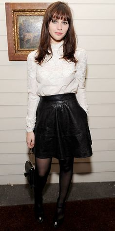 Felicity Jones in a leather skirt with a high-neck blouse and added black accessories.