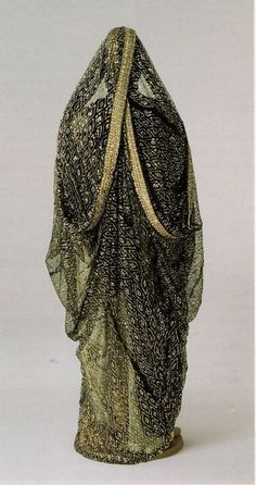 Seen from the back: a black net thawb embroidered with sequins, the sleeves are draped over the head, forming a head cover. This festive dress is from the Eastern Province, Saudi Arabia.