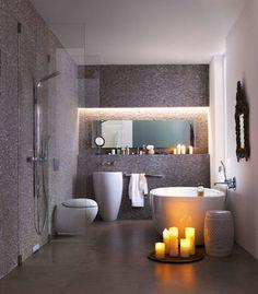 Douche italienne avec système évacuation de l'eau vertical installée dans une salle de bain grise au design épuré.