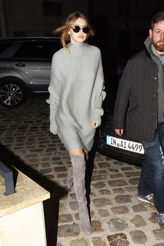 Gigi Hadid wears a gray sweater dress with round sunglasses and thigh-high suede boots