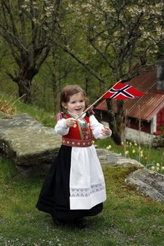 Girl in traditional Norwegian clothing and holding Norway's flag.