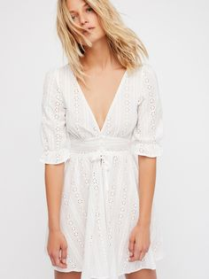Cotton Eyelet Dress   This light and easy cotton eyelet sundress is the sweetest mini dress featuring a puff sleeves with ruffle trim.  * Plunging neckline * Center button closures * Decorative tie detail * Full skirt * Fitted silhouette * Lined