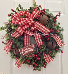 Its a little bit country! A little bit down on the farm with its large bow of red and white plaid ribbon. Mixed in with the evergreen branches are boxwood and berry branches. Three large rusted Christmas bells are surrounded by lots of large winter berries. Interspersed are large pine cones. Sprigs of ivy help to make this wreath very full. A little rustic sign hangs from the branches saying, Merry Christmas! If you like the country look, then this is the Christmas wreath for you! The…
