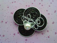 Broche hecho con capsulas Nespresso negras, alambre y perla