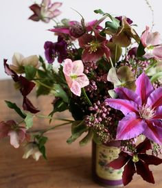 fuschia clematis as the star of this arrangement of hellebores and lilac by amy merrick