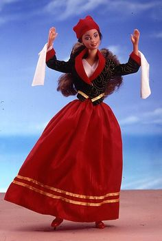 Say yah-soo, or hello, to Greek Barbie doll. She is ready for a night of dancing in her traditional Greek ensemble. Her floor-length red skirt is trimmed with golden accents. Over her white blouse, Barbie wears a fitted black jacket with red collar and cuffs. Her hair is pulled back, and topped with a red cap.
