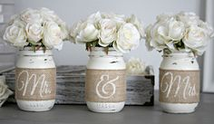 This particular set of rustic wedding or engagement party table centerpieces feature pint sized Mason jars expertly hand painted, lightly distressed, sealed, and finished with hand painted burlap with