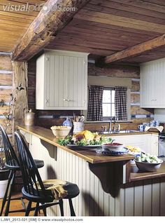 Like this cabin kitchen:-)  love the painted breadboard alongside the logs and chinking.