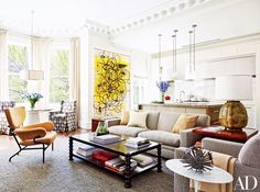 Open living room with large art, a gray sofa and matching armchair