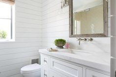 Gorgeous guest bathroom features shiplap walls lined with a rustic beveled mirror illuminated by Sabine Wall Sconces over a wall-mount faucet and a white washstand topped with honed white marble facing a walk-in shower filled with white herringbone tiles.