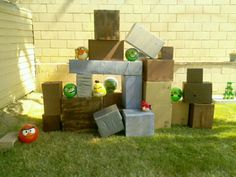 Life-size Angry Birds game.. I collected different size boxes from local stores and spray painted some brown(wooden block effect) and some light blue(glass effect). For the green pigs, and red & yellow Angry Birds we simply bought toy balls and painted them ourselves with acrylic craft paint.