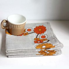 Six 1970s napkins from natural linen (or linen mix) fabric with a printed floral band in orange, brown and white. Good condition, the napkins have