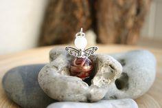 niedlicher kleiner Schutzengelanhänger, das Köpfchen ist eine Kunststoffperle (Polaris), der Bauch eine Glasperle, die Flügel sind aus Tibetsilber