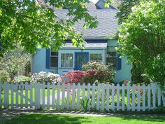 Cute cottage with a white picket fence that really frames the house.