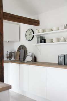 White, simple kitchen, but I dislike the open shelves as they collect greasy dust in kitchens