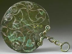 One of the most beautiful items of Celtic treasure are mirrors. These were owned by well-off ladies and were made of bronze. One side was polished brightly for the lady to see herself. The back and handle were usually decorated, with engraved lines and shapes. Often spaces between lines were filled with 'hatching' - little marks cut into the bronze, to make an area 'darker', so the overall pattern stands out better. It is these decorations that make many Celtic mirrors great works of art.