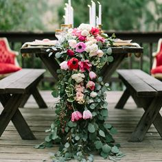 A table runner of fresh flowers flows onto the ground at a casual outdoor wedding - notice the picnic table and benches