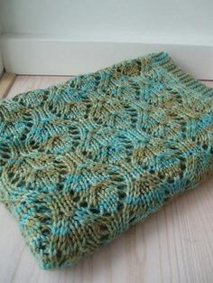 "This beautiful baby blanket takes only two skeins of yarn. Yes, you read that right. Only TWO skeins! This delicate baby blanket features a simple yet beautiful lace pattern with a garter stitch border. It calls for a worsted weight yarn knit loosely on size 10 needles. Shepherd Worsted is a great choice for the blanket and comes in a fun array of hand dyed colors. We even have our own exclusive colorway, aptly named ""ImagiKnit""! Malabrigo Rios is another great option for the blanket i..."