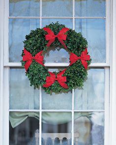 This wreath made with boxwood and embellished with a quartet of slim satin bows captures the classic Christmas pairing of red and green.