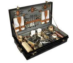A fine cased Coracle brand picnic set for six persons, by G W Scott & Sons, 1920s, black leather-cloth and wicker framework interior fitted with large leather-covered vacuum flask, a large wicker-covered drinks bottle, a smaller milk bottle, three enamel based food boxes, four other food tins of assorted sizes, set of six stacking wicker-cased glasses, cups and saucers by Bisto, and ceramic butter and preserves jars, with rectangular enamel plates and cutlery housed behind leather straps