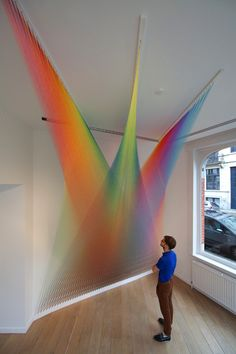 thousands of single strands of thread are hooked into walls to collectively form brilliant prisms