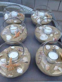 Bonito centro de mesa de estilo playa hecho con arena, caracoles y una vela. OJO! No acercar mucho la estrella de mar a la llama porque desprender un olor nada agradable