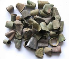 A variety of thimbles spanning the centuries from medieval handmade ones in copper and bronze to mass produced ones from the industrial revolution of the 19th century. There are open ended ones, lead topped ones and even a couple of silver ones.
