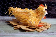 CHICKY CHEESE BALL. Ingredients: cream cheese, cheddar jack cheese, chopped chives, red chiili flakes or paste. Decorate with shredded cheddar feathers, raisin eyes, carrot strip comb/wattle/feet and sunflower seed beak on a nest of crackers.   Posted by The Egg Farm, 4/18/2013