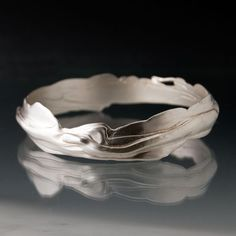 Solid Sterling Silver Flow Bracelet Bangle: Flow is a beautiful collection that unites two profound themes: femininity and fluidity. Inspired by water ripples, flowing rivers and gentle cascades, it is a consciously tactile suite. Every bracelet is as unique as the wearer. The actual flow lines will vary on each individual piece. No two bracelets are ever exactly the same.    This shown bracelet is available in medium size, oval shaped ( 2 1/2 or 6.4 cm by 2 3/8 or 5.9 cm) and is 4m...