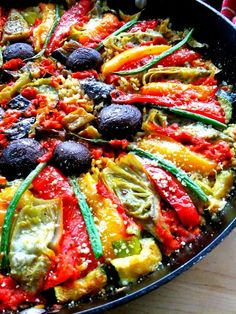 Vegetable Paella, Italian Style - 1½c short grain arborio rice; 4c warmed chicken stock; 1c roasted red pepper puree made from 4 peppers; 1 medium eggplant; 1 zucchini; 1 each, red, yellow & orange bell pepper cut in strips 8oz. crimini mushroom caps; 1 bag frozen artichoke hearts; a handful of haricot vert beans; 1-4 garlic cloves, minced; 1 medium onion; olive oil; grated Romano or parmesan cheese; chopped basil for garnish