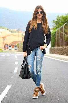 Something as simple as opting for a black oversized sweater and blue ripped skinny jeans can potentially set you apart from the crowd. Rock a pair of khaki leopard high top sneakers for a more relaxed aesthetic. Shop this look on Lookastic: https://lookastic.com/women/looks/oversized-sweater-skinny-jeans-high-top-sneakers-tote-bag-sunglasses-watch/13038 — Black Sunglasses — Black Oversized Sweater — Gold Watch — Blue Ripped Skinny Jeans — Black Leather Tote Bag — Tan Leopard High To...