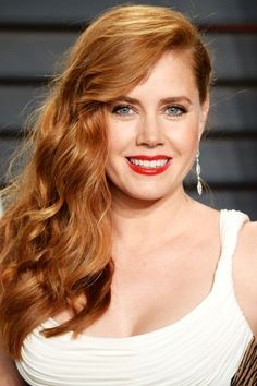 Actress Amy Adams red hair looks gorgeous swept in waves to the side paired with a bright red lip gloss.
