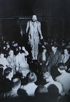 """Levitation. Colin Evans gave demonstrations at spiritualist meetings in the 1930's. The audience sat in darkness and could see Evans by reflective tape on his feet and wrists. Photographer unknown.   Flickr commenter on this pic contends """"most of the photos are produced from simple darkroom tricks. This one is a man jumping on a chair, the effect achieved when the chair was burned off the print with a pen light. Notice the wire in his left hand. That is the remote button for the camera"""""""