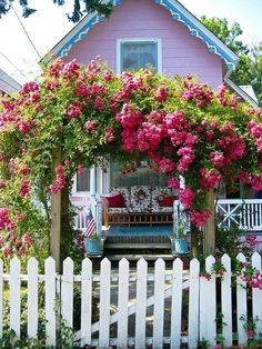 White picket fence, rose trellis with wine colored roses, pink cottage, adorable porch.. Get the picture?  Dreamy