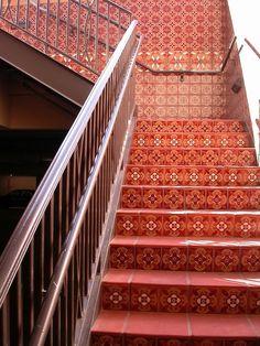 "Red! Beautiful stairway in a public parking garage. ""Debris Series Recycled Tile"" - Cuerda Seca Steps at Bay Meadows, CA. #tile #staircase #stairs #steps #stairway #riser #Mexican #red"