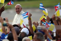 People wave Cuban and Papal flags as Pope Francis passes by as he arrives to perform Mass on September 20, 2015 in Revolution Square in Havana, Cuba. Pope Francis is on the first full day of his three day visit to Cuba where he will meet President Raul Castro and hold Mass in Revolution Square before travelling to Holguin, Santiago de Cuba and El Cobre then onwards to the United States.