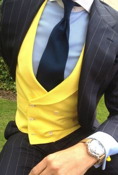 Tap into refined, elegant style with a black vertical striped suit and a yellow waistcoat.   Shop this look on Lookastic: https://lookastic.com/men/looks/suit-waistcoat-dress-shirt-tie-watch/13023   — Light Blue Dress Shirt  — Navy Tie  — Yellow Waistcoat  — Black Vertical Striped Suit  — Tan Leather Watch