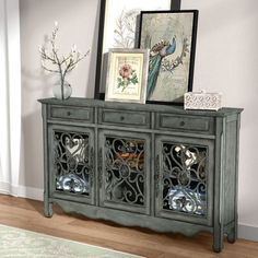Effortlessly balance ornate style and welcoming, weathered charm in your space with this eye-catching sideboard, the perfect piece for your Provencal-tinged cottage aesthetic. Featuring a curving skirt and bold scrollwork cabinet fronts, this piece brings bold definition to your room, while its neutral gray finish lets you blend it in with any palette. Set it against a beige or off-white wall in the dining room to lean into the neutral palette, then top it off with cherished china and turned…
