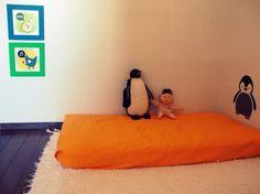 quarto montessoriano de tema pinguim bem simples para bebês e crianças de até 2 anos: um colchão no chão, um tapete limpo para amortecer a queda caso a criança role durante a soneca. os quadros ficam na altura dos olhos da criança para que ELA possa desfrutar da decoração do quarto e os brinquedos são sempre poucos, para que ela aproveite o que tem e consiga desfrutar do seu próprio espaço.