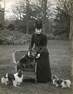 H.M. Queen Alexandra at Sandringham with her Chow Chow, Plumpy, on a wicker chair, and two of her Japanese Chins. Date: 1896