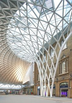 steel tree columns radiate upward into a single-span roof structure; King's cross station, UK.