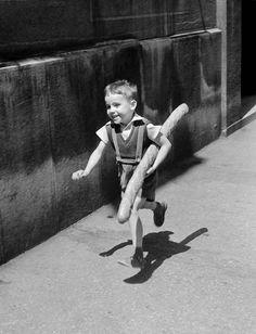 A tiny Parisian boy brings home a baguette for supper.