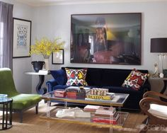 The living area includes a sofa  by Ralph Lauren Home flanked by vintage side tables and topped with pillows made from a vintage ikat; the velvet slipper chair is  from the designer's Carolina George line, the wood table is by Josef Hoffmann, the photograph is by Malerie Marder, and the walls  are painted in Benjamin Moore's Alaskan Husky